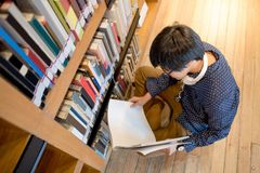 Young Asian man university student reading book in library. Young Asian man student reading book in library, education research and self learning in university Royalty Free Stock Photography