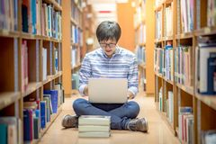 Young Asian man student using laptop in library. Young Asian man university student thinking about his project homework and using laptop computer in library Royalty Free Stock Photo