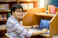 Young Asian man university student using laptop in library. Young Asian man university student thinking about his project homework and using laptop computer in Royalty Free Stock Image