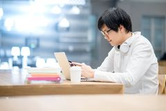 Young Asian man university student using smartphone in library. Young Asian man university student using smartphone while doing homework with his laptop computer Stock Images