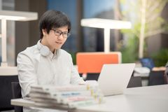 Young Asian man university student working in library Royalty Free Stock Photography