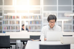 Young Asian man university student working in library Royalty Free Stock Image