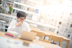 Young Asian man university student working in library Stock Photos