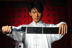 Young Asian Man unsheading a sword Stock Photography