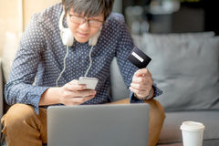 Young Asian man using credit card for online shopping Royalty Free Stock Photos