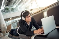 Young man listening to music waiting in airport terminal Royalty Free Stock Photography