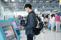 Young asian man using self check-in kiosks in airport Stock Photos