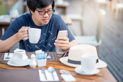 Young Asian man using smart phone during having breakfast Stock Photos