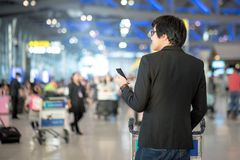 Young asian man using smartphone in airport terminal Royalty Free Stock Image
