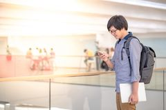 Young Asian man using smartphone in shopping mall. Young Asian man dressed in casual style using smartphone and holding laptop computer in shopping mall, modern Royalty Free Stock Images