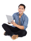 Young asian man using tablet pc while sitting on the floor, isol Royalty Free Stock Photo