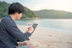Young Asian man using tablet on the beach. Young Asian man using tablet on tropical beach, digital nomad or freelance lifestyle concepts Stock Images