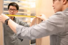 Asian man using tape measure on modern closet. Young Asian man using tape measure for measuring mirror on modern wooden cabinet in walk-in closet showroom royalty free stock photography