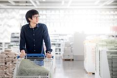 Young Asian man using trolley cart in warehouse. Young Asian happy man using trolley cart choosing what to buy. Shopping home improvement stuff in warehouse Royalty Free Stock Image