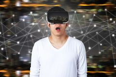 Young asian man with virtual reality goggles. A young Asian man in casual white outfit wearing VR glasses watching video with open mouth feeling excited, shocked royalty free stock photography