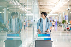 Young asian man walking with airport trolley Stock Image