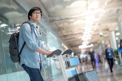 Young asian man walking with trolley in airport terminal Royalty Free Stock Photography