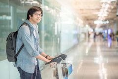 Young asian man walking with trolley in airport terminal Stock Photography