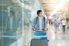 Young asian man walking with airport trolley Stock Photography