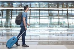 Young asian man walking and pulling the suitcase royalty free stock image