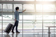 Young Asian man with luggage in airport terminal. Young Asian man walking with suitcase luggage in the airport terminal pointing the plane taking off, travel Stock Images