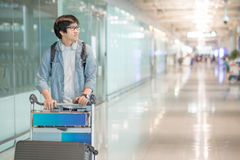 Young asian man walking with trolley in airport terminal Stock Images