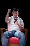 Young asian man watching to smart phone screen cheer up somethin. G with exciting emotion Stock Photography