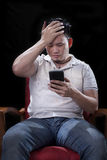 Young asian man watching to smart phone screen with unhappy and Royalty Free Stock Image