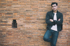 Young asian man wearing black jacket and blue jeans standing aga. Handsome young asian man wearing black jacket and blue jeans standing against old orange brick royalty free stock photography