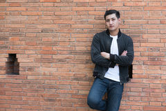 Young asian man wearing black jacket and blue jeans standing aga. Handsome young asian man wearing black jacket and blue jeans standing against old orange brick stock photos