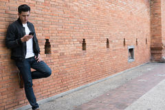Young asian man wearing black jacket and blue jeans standing aga Royalty Free Stock Photo