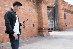 Young asian man wearing black jacket and blue jeans standing nea. Handsome young asian man wearing black jacket and blue jeans standing near old orange brick royalty free stock photography
