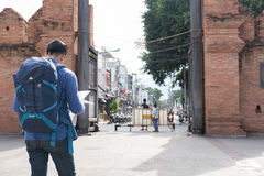 Young asian man wearing blue jacket and jeans reading map while. Chiang Mai, Thailand - June 29, 2017: young asian man wearing blue jacket and jeans reading map Stock Images