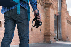 Young asian man wearing blue shirt and jeans with camera and bac. Kpack standing near old orange brick wall Stock Photo