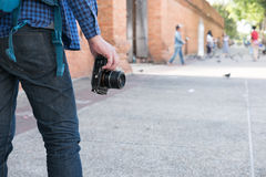 young asian man wearing blue shirt and jeans with camera and bac Stock Photos