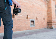 Young asian man wearing blue shirt and jeans with camera and bac. Kpack standing near old orange brick wall Royalty Free Stock Photo