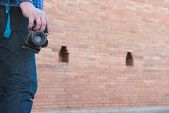 Young asian man wearing blue shirt and jeans with camera and bac. Kpack standing near old orange brick wall Royalty Free Stock Images