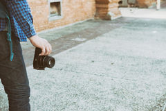 Young asian man wearing blue shirt and jeans with camera and bac. Kpack standing near old orange brick wall Royalty Free Stock Photos