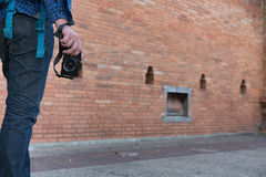Young asian man wearing blue shirt and jeans with camera and bac. Kpack standing near old orange brick wall Stock Image