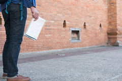 Young asian man wearing blue shirt and jeans with map and backpa. Ck standing near old orange brick wall Royalty Free Stock Image