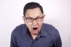 Young Man Shouting, Anger Gesture. Young Asian man wearing blue shirt shouting because of anger. Against white wall human one single indonesian malaysian chinese royalty free stock photo