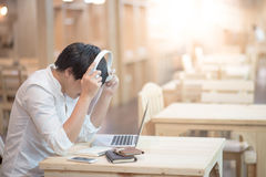 Young Asian man wearing headphones listening to music. Young Asian happy man wearing headphones listening to music and working on modern laptop computer in Royalty Free Stock Photo