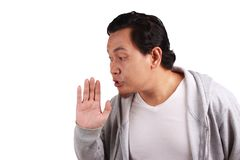 Man Whispering Gossiping. Young asian man wearing jacket whispering and gossiping stock photography