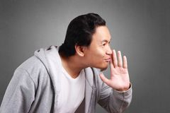 Man Whispering Gossiping. Young asian man wearing jacket whispering and gossiping stock image