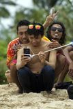 Young asian man wearing sunglasses takes selfie with friends. Young asian man wearing sunglasses takes selfie with using selfie stick in front of palm trees and Royalty Free Stock Photo