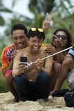 Young asian man wearing sunglasses takes selfie and laugh with friends. Young asian man wearing sunglasses takes selfie with using selfie stick in front of palm Stock Image
