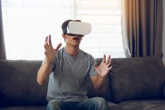 Young asian man wearing virtual reality glasses at living room for admiring virtual reality stock photos