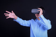 Young Asian man wearing virtual reality goggles. With black background studio grab something in mid air pose. Smartphone using with VR headset stock image