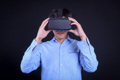 Young Asian man wearing virtual reality goggles. With black background studio. Smartphone using with VR headset royalty free stock photo