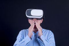Young Asian man wearing virtual reality goggles. With black background studio. Smartphone using with VR headset royalty free stock photography